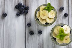 Yogurt wit blueberries & sliced bananas. In a glass jar, topped with honey and mint flat lay stock images