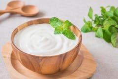 Yogurt in wooden bowl Stock Photo