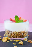 Yogurts glass with cereals and strawberries,pink background Royalty Free Stock Photography
