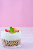 Yogurts glass with cereals and strawberries,pink background Royalty Free Stock Photos