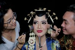 A Sinden, an artist who specializes in singing traditional Javanese songs, conducts a photo session with make-up artists