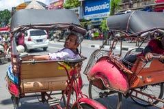 Yogyakarta, Indonésia - o motorista idoso do riquexó está procurando clientes na estrada de Malionoro em Yogyakarta imagem de stock