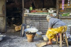 Poor old woman cooking street food royalty free stock photos
