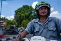 Yogyakarta, Indonesia - March 16, 2018: Scooter driver waiting for the green light on Malioboro Road. Yogyakarta, Indonesia - March 16, 2018: Scooter driver Royalty Free Stock Images