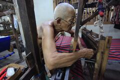 Oldest worker checks woven fabric