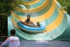 Adults and A Child Fear Expression on Water Slide. Yogyakarta, Indonesia, 28th March 2017: Adults and a child fear expression on water slide Jogja Bay Royalty Free Stock Photos