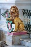 YOGYAKARTA, INDONESIEN - AUGUST, 28: Sitzender Löwe nahe Eingang Lizenzfreies Stockfoto
