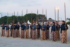 YOGYAKARTA INDONESIEN - CIRCA SEPTEMBER 2015: Ceremoniella Sultan Guards i sarongs som står med spjut som är främsta av Sultan Pa arkivbild