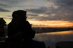 Yogyakarta Indonesien - mars 16, 2018: Muslimsk kvinna som tycker om solnedgång på pölen Royaltyfri Fotografi