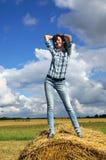 Yoing kvinna i höstackar på fält Arkivfoto