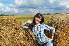 Yoing woman in haystacks on fields Royalty Free Stock Photo