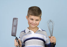 Yoiung boy holding kitchen utensils smiling. Royalty Free Stock Photography