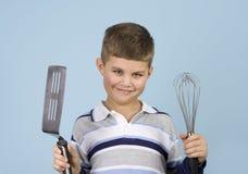 Yoiung boy holding kitchen utensils smiling. Yoiung boy holding kitchen utensils (spatula and whisk) while smiling. Blue background royalty free stock photography