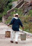 Yoking buckets of water. Elderly man walking with yoke and two tin buckets filled with water Royalty Free Stock Images