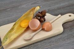 Yolk and albumen. Egg in a corn leaf on the cutting board, hazelnut. Egg Stock Photography