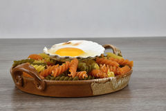 Yolk and albumen. Egg in sea shells in a bowl of pasta on the wooden background. Stock Images