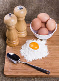 Yolk, eggs of house hens, spoon, salt and pepper. With wheat flour on kitchen to a board Stock Image