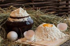 Yolk in flour. Broken egg. White egg. Flour in a clay pot. Flour Stock Photo