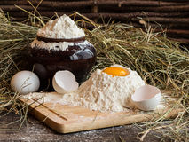 Yolk in flour. Broken egg. White egg. Flour in a clay pot. Stock Photography