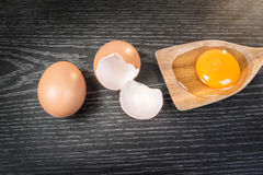 Yolk in wooden spoon on wooden background.  royalty free stock photography