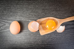 Yolk in wooden spoon on wooden background.  stock images
