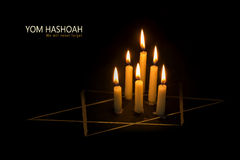 Yom Hashoah, burning candles and the star of David against blac. Six burning candles and the star of David against black background, text Yom Hashoah, the Jewish royalty free stock photos