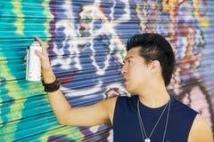 Yong asian male grattiti artist. Young asian male vandalising a wall with graffiti Stock Photo