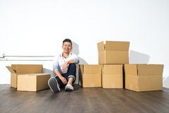 A yong asian man sitting on floor smiling with boxes Stock Images