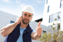 Yong attractive worker using mobile phone  on a construction sit Stock Images