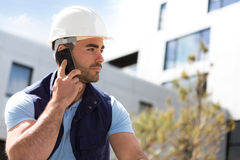 Yong attractive worker using mobile phone  on a construction sit Stock Photography
