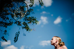 Yong blond girl looks up at basketball goal. Royalty Free Stock Image