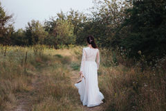 Yong bride spinning in a white dress on the bank on nature. Dress develops in the wind. Happy bride in a wedding dress is spinning Royalty Free Stock Image