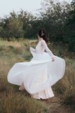 Yong bride spinning in a white dress on the bank on nature. Dress develops in the wind. Happy bride in a wedding dress is spinning Royalty Free Stock Images