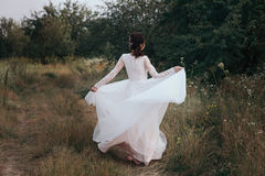 Yong bride spinning in a white dress on the bank on nature. Stock Photos