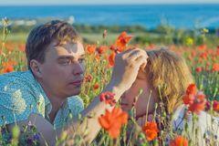 Yong couple with flowers near the sea. Royalty Free Stock Photography