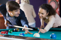 Yong couple hit one ball in billiards, and look at each other. f Royalty Free Stock Photo
