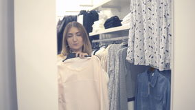 Yong girl choosing clothes and looking to mirror in mall or clothing store. stock video