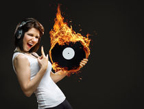 Yong girl with headphones and burning record in hands Royalty Free Stock Photos