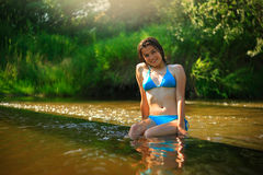 Yong girl relaxing in the forest river Royalty Free Stock Photography