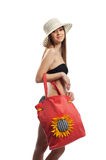 Yong girl walk with red beach bag and straw hat. Yong woman posing with beach bag and straw hat isolated Royalty Free Stock Images