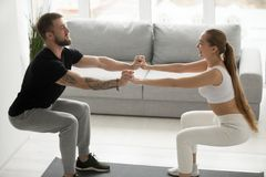 Young sporty couple doing squats holding hands together at home. Yong happy sporty couple doing squats together at home, men and women holding hands working out Royalty Free Stock Photo