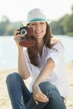 Yong hipster girl shooting with old camera at the beach. Royalty Free Stock Photos