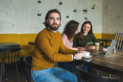 Yong hipster male and females in cafe working with laptop. With coffee on wooden table Royalty Free Stock Image