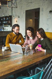 Yong hipster male and females in cafe working with laptop. With coffee on wooden table Royalty Free Stock Photography