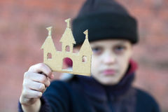 Yong homeless boy holds a cardboard castle Royalty Free Stock Photos