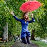 Yong kobieta skacze z czerwonym parasolem obrazy stock