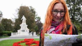 Yong kobiety turysta z czerwonym włosy i szkło przyglądająca mapa w Burggarten, Wiedeń, Austria Obraz Royalty Free