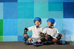 Yong little athletic boys on roller sitting against the blue graffiti wall. Rollerblading child stock photography