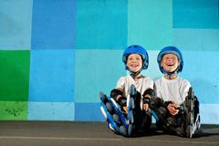 Yong little athletic boys on roller sitting against the blue graffiti wall. Rollerblading child stock image