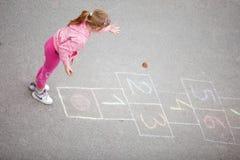 Yong mała dziewczynka na hopscotch Zdjęcie Stock